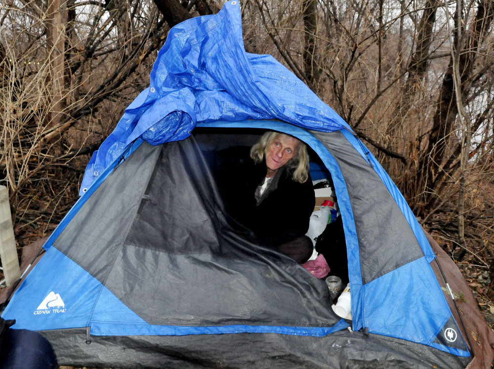 Vaughan Orchard, who is homeless, peers out from his tent where he lives beside the railroad tracks and Kennebec River in Waterville on a cold and rainy Tuesday.