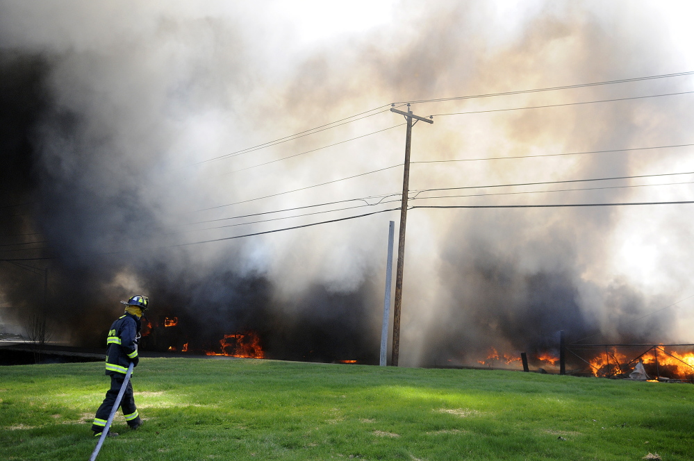 A firefighter drags a hose to an explosion May 5 while attempting to fight the blaze that destroyed AD Electric on South Monmouth Road in Monmouth.