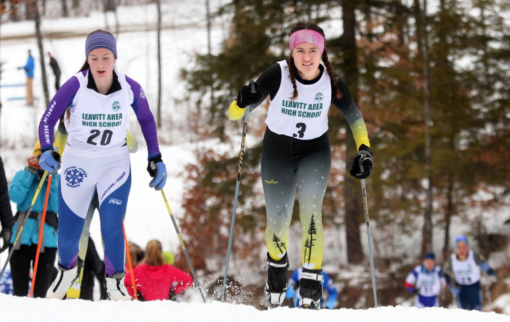 Maranacook's Jaycee Greeley (3) passes Phoebe Bell of Deering during an up-hill portion of the Leavitt Hornet Classic at Quarry Road Trails in Waterville on Saturday.