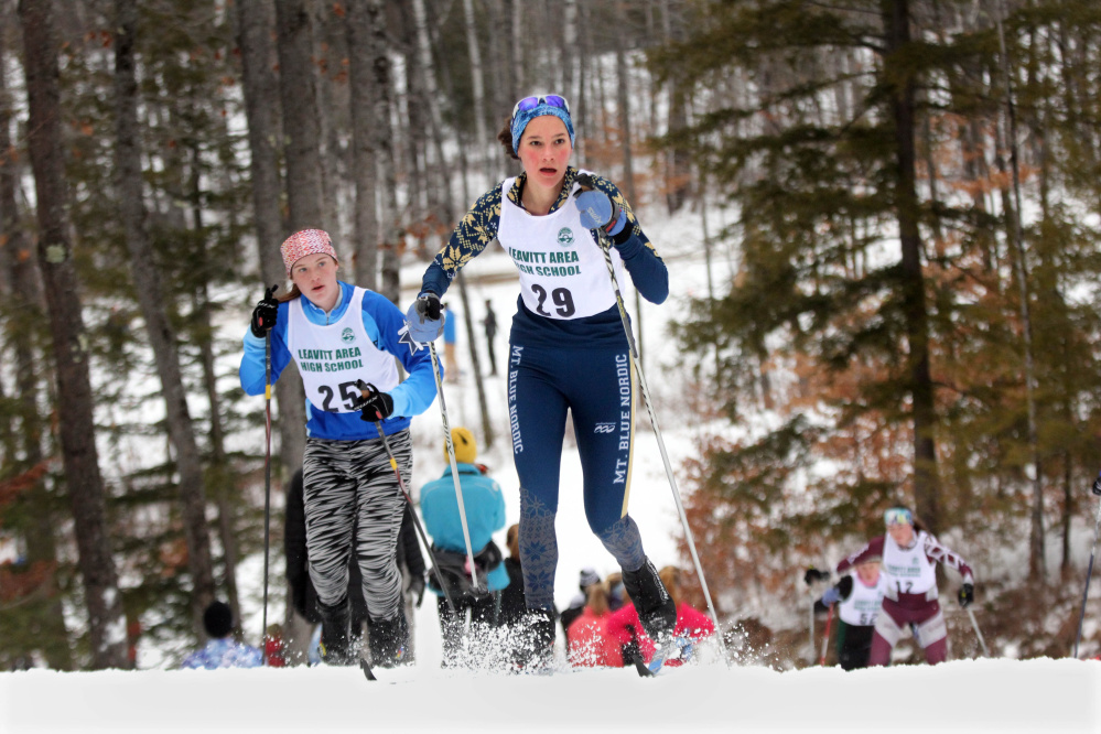 Mt. Blue High School's Meg Charles climbs a hill ahead of Telstar's Kaitlyn Brown during the Leavitt Hornet Classic on Saturday the Quarry Road Trails in Waterville. Charles finished 11th.