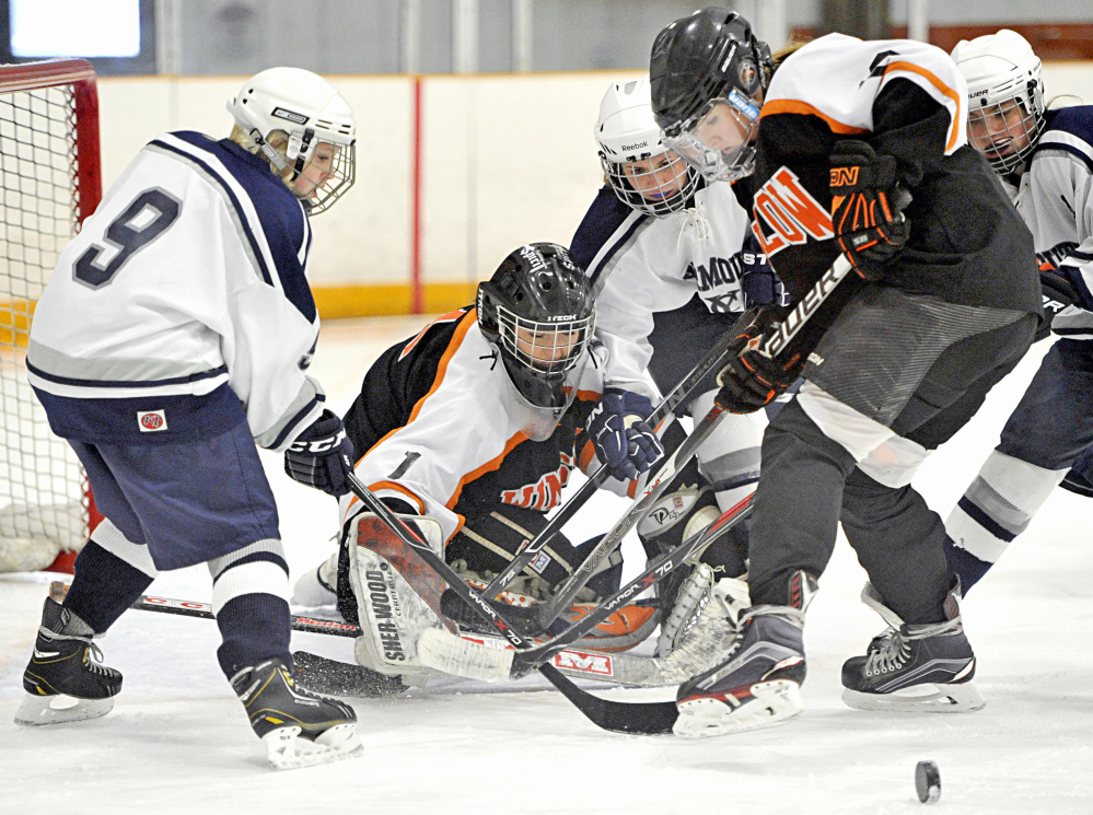 Yarmouth's Madison McCallum, left, tries to get control of the puck in front of Winslow goalie Kiana Richards as Yarmouth's Keely Arnold, Winslow defenseman Bailey Robbins and Yarmouth center Colleen Sullivan converge on the action during a game Saturday.