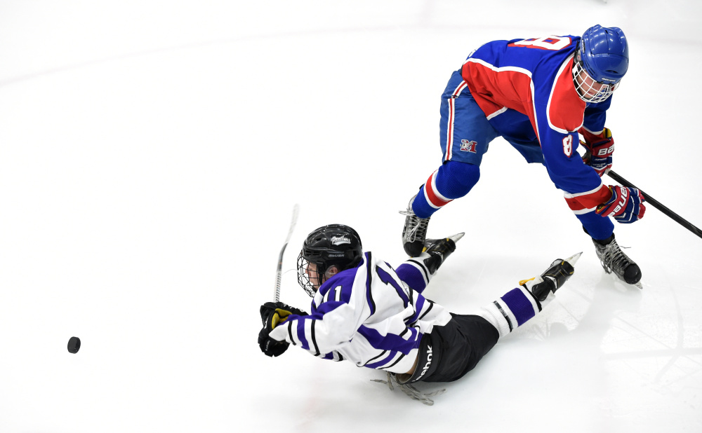Waterville Senior High School's Jackson Aldrich (11) gets knocked to the ice by Messalonskee High School's Dylan Burton (8) in the third period in the Class B North regional final Tuesday at Alfond Arena at the University of Maine at Orono.