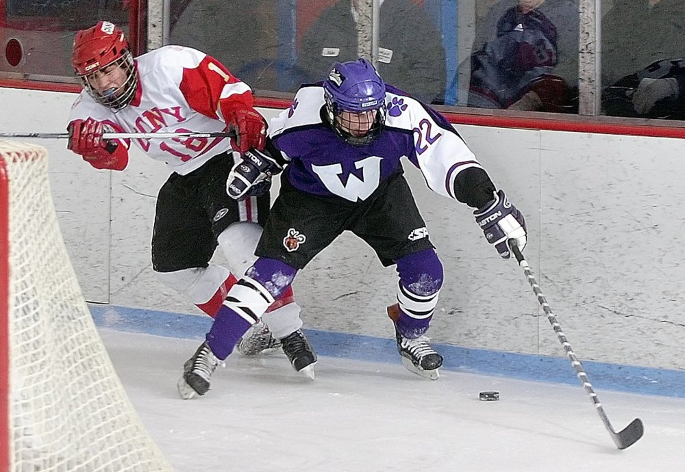 Cony's Derek Brotherton, left, and Waterville's Eric Aldrich battle for a puck behind the Cony net during a 2009 game night at the then-Kennebec Ice Arena in Hallowell.