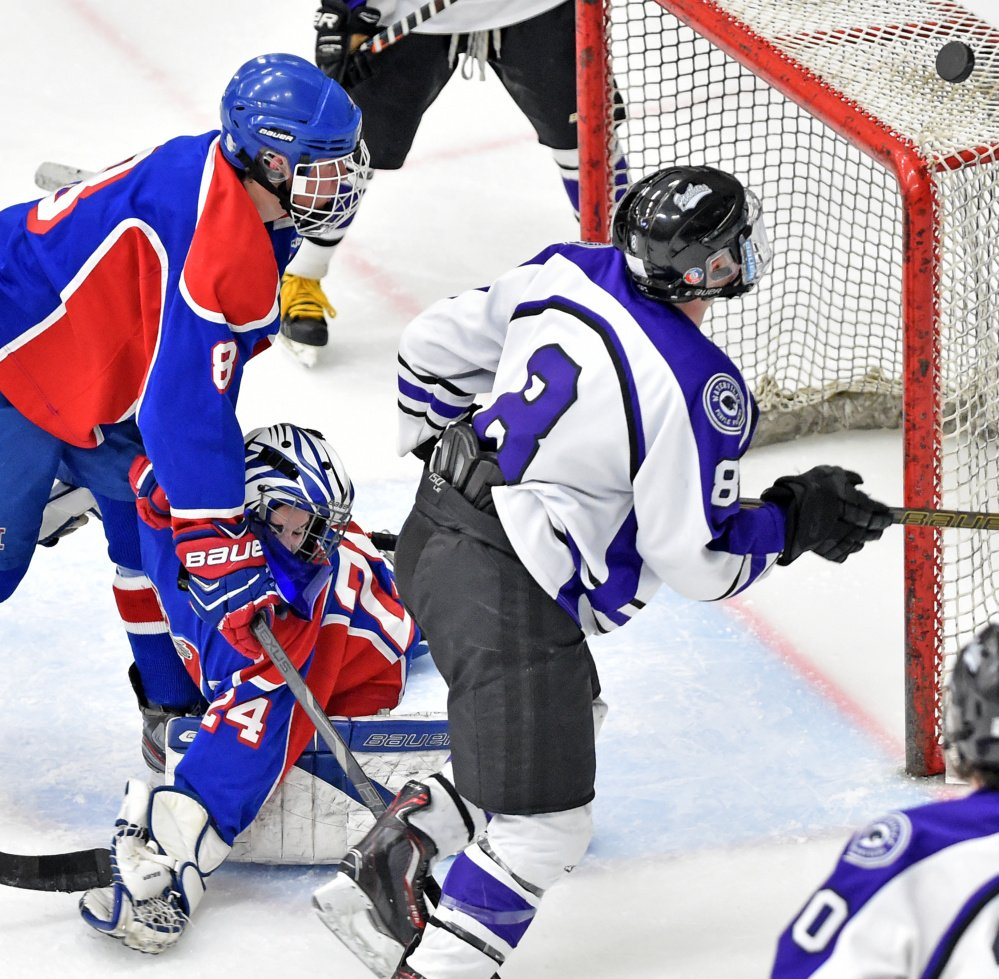Waterville Senior High School's Justin Wentworth (8) tries to handle the puck as he tries to score on Messalonskee High School goalie Amber Kochaver in the Class B North regional final Tuesday at Alfond Arena at the University of Maine at Orono.