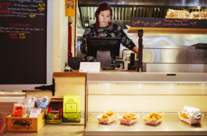 """Ambre Davidson works the register at the Hilltop Superette in Portland on Wednesday. She would appreciate an increase to a $12 minimum wage. """"I have a 4-year-old, and a couple dollars extra an hour would be a huge thing for me, especially with child care,"""" she said."""
