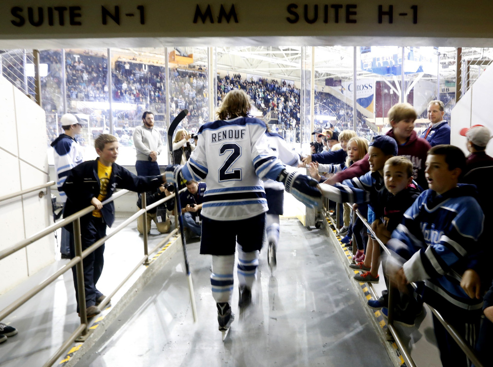 University of Maine defenseman Dan Renouf gets some good vibes from young fans before a game against North Dakota during the Ice Breaker tournament at Cross Insurance Arena last fall. Despite the team's recent struggles, UMaine finds plenty of support.