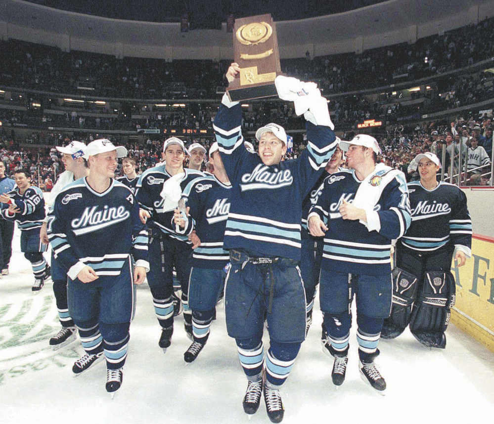 In the glory days of the University of Maine's hockey program, Marcus Gustafsson, who scored the game-winning goal in the NCAA Division I championship game in 1999, is surrounded by teammates as he hoists the trophy in Anaheim, Calif.
