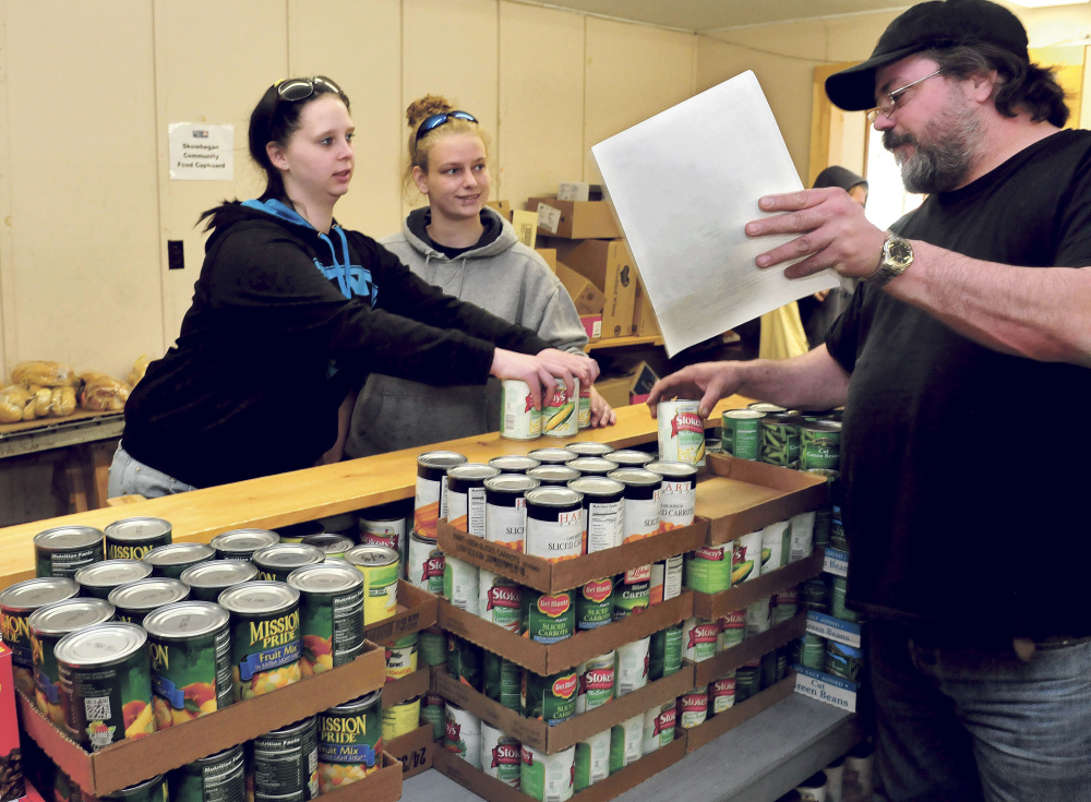 Brittany Ward, left, and Andrea Rowe receive food items Wednesday from volunteer Ty Parson at the Skowhegan Food Cupboard.