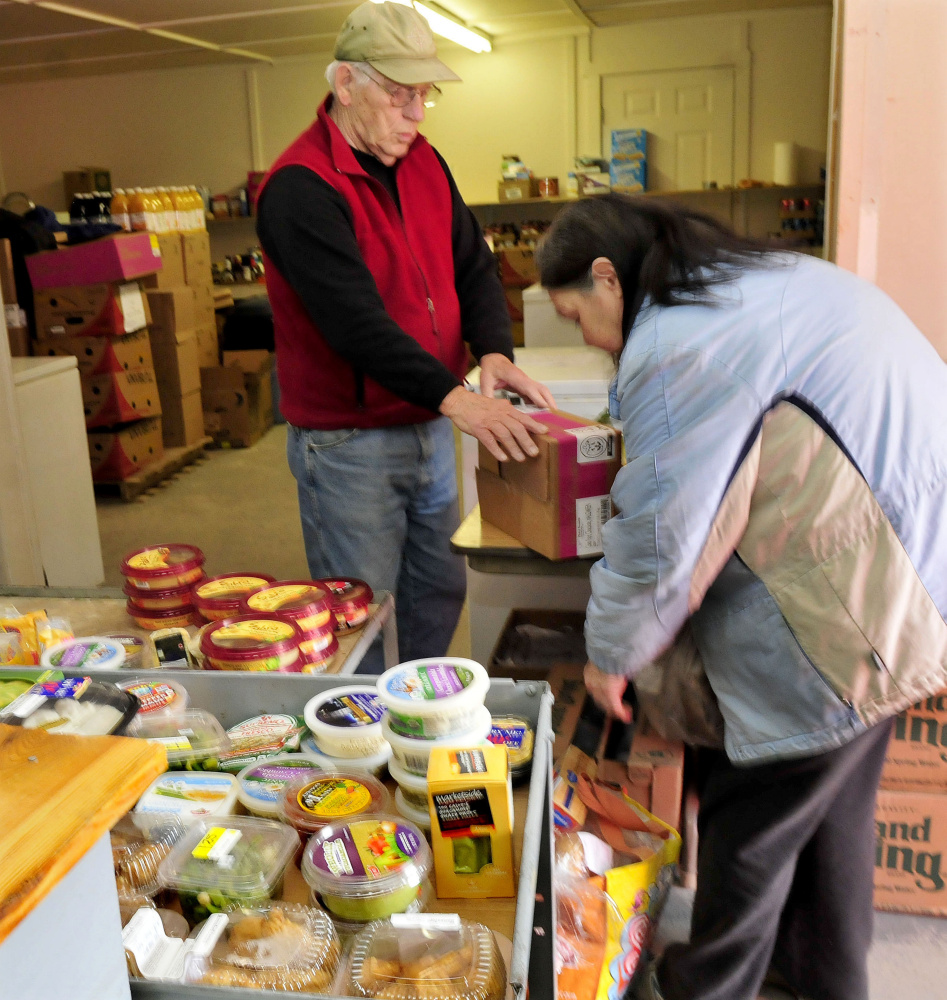 Skowhegan Food Cupboard volunteer Richard Boone helps client Kathy Searles with food items on Wednesday.