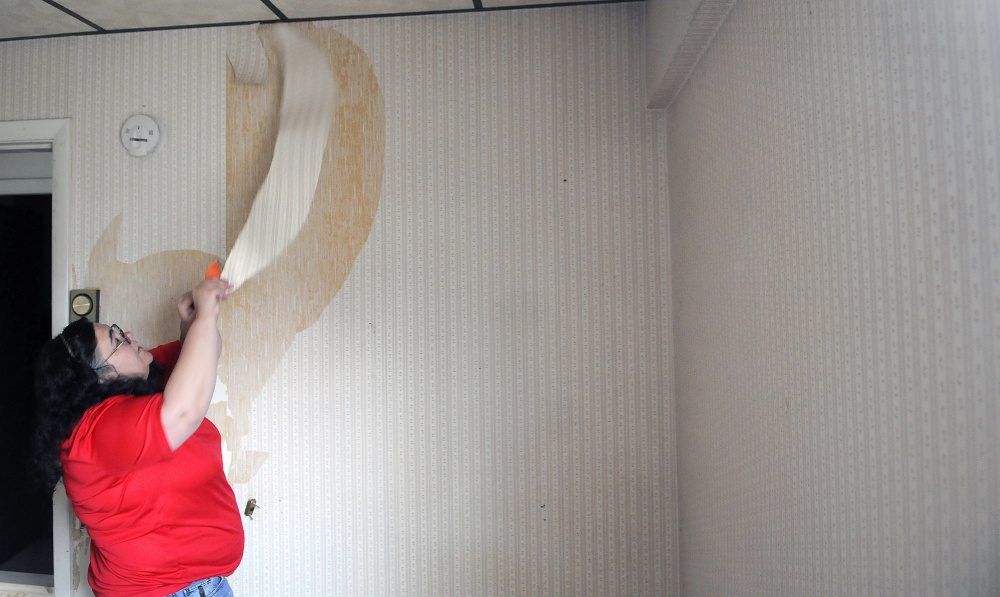 Volunteer Karen St. Peter strips wallpaper Wednesday from a room at 8 Summer St. in Augusta. The building is being converted into a shelter and transitional housing for female veterans as the Betsy Ann Ross House of Hope.