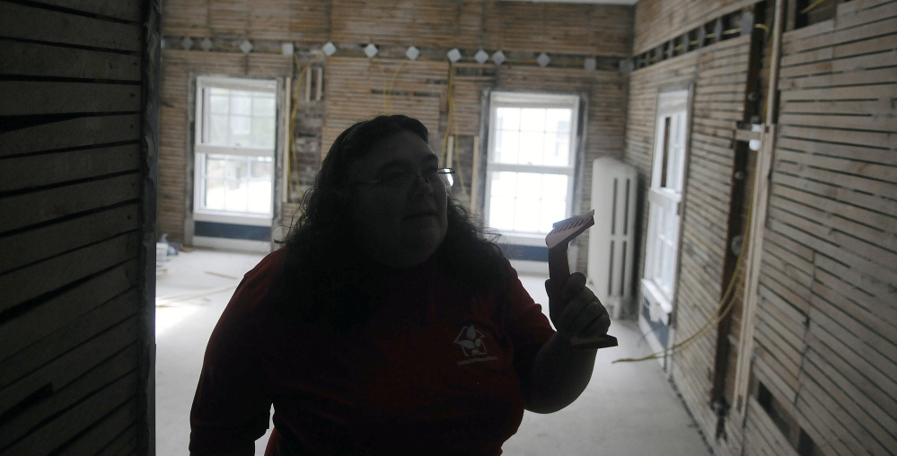 Volunteer Karen St. Peter walks Wednesday through a stripped room at 8 Summer St. in Augusta. The building is being converted into a shelter and transitional housing for female veterans as the Betsy Ann Ross House of Hope.