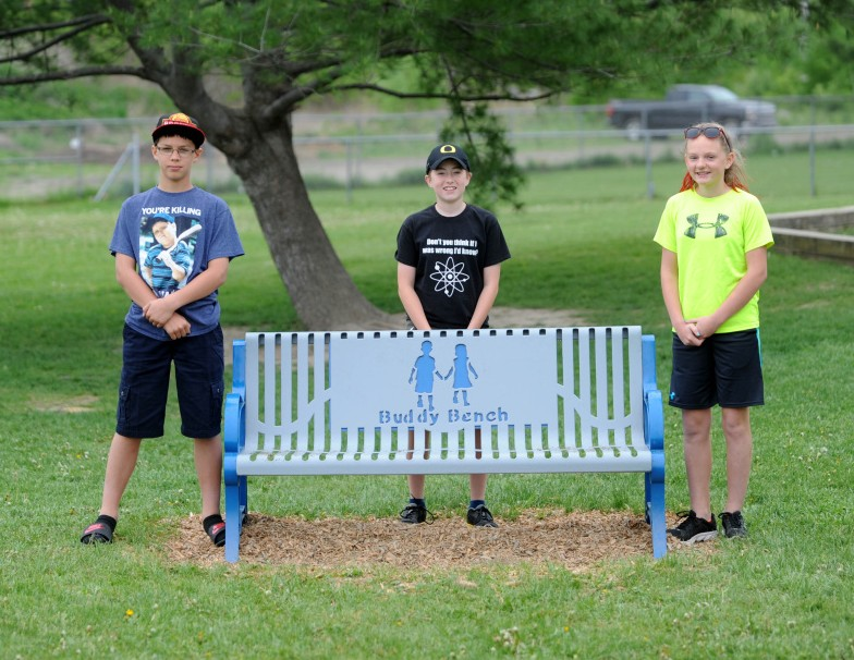 Benton Elementary School sixth-grade Student Council officers, from left, Andrew Trombley, 12, Corbin Kissinger, 12, and Taylor Wilkie, 12, pose for a portrait Friday in front of a buddy bench on the playground at Benton Elementary School. Students who are new to the school or feel lonely can sit on the bench, and other students will join them.