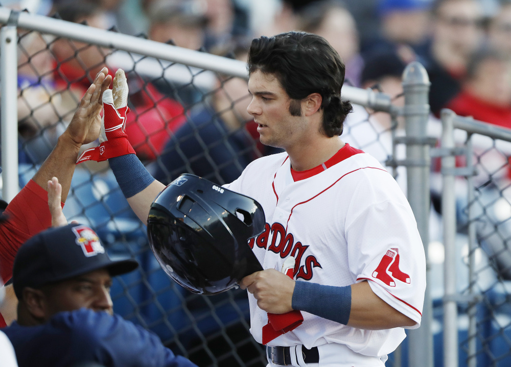 Andrew Benintendi is congratulated after scoring a run during the fifth inning Tuesday. Benintendi had 2 RBI in the Sea Dogs win.    Joel Page/Staff Photographer