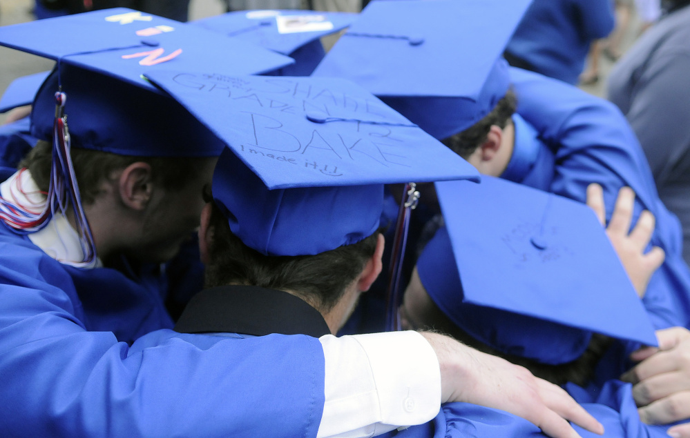 Messalonskee High School seniors huddle before graduation Thursday at the Augusta Civic Center.