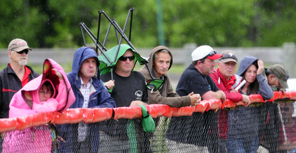 Fans take cover along the third base line at Cony Family Field in Augusta as rain began to fall during the Class C/D senior all star game Thursday at Cony Family Field in Augusta.