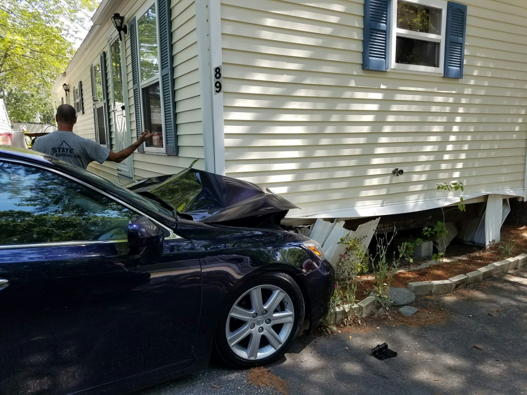 A car is wedged under a trailer home in Scarborough on Monday. (Courtesy Scarborough Fire Department)