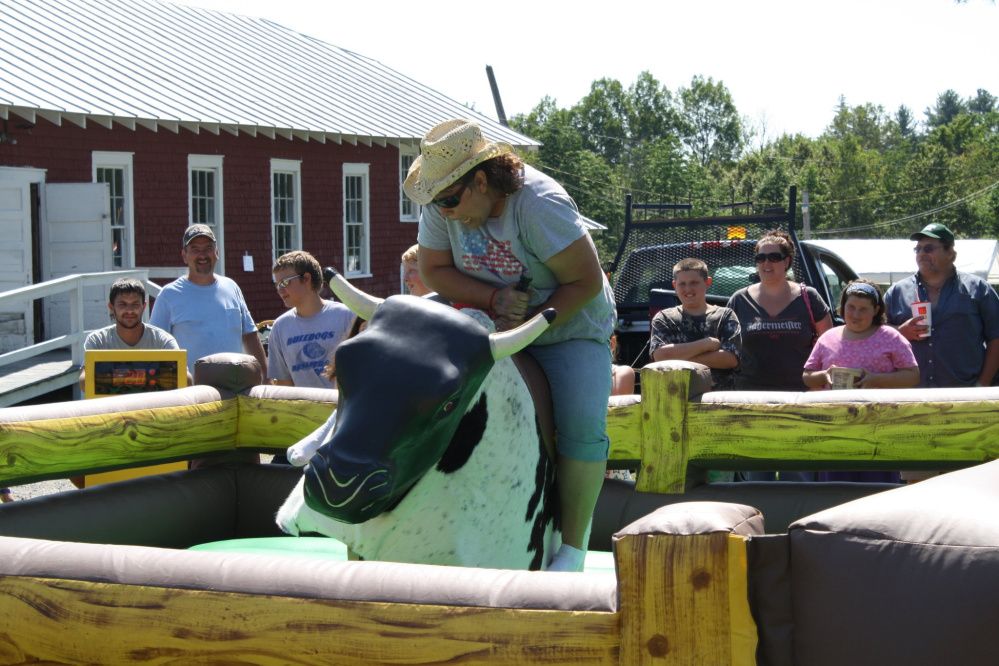 Athens Recreation Department organizer Victoria Avery rides a mechanical bull during a previous year's Family Fun Day. This year's events are set to begin at noon Saturday at the fairgrounds on Main Street.