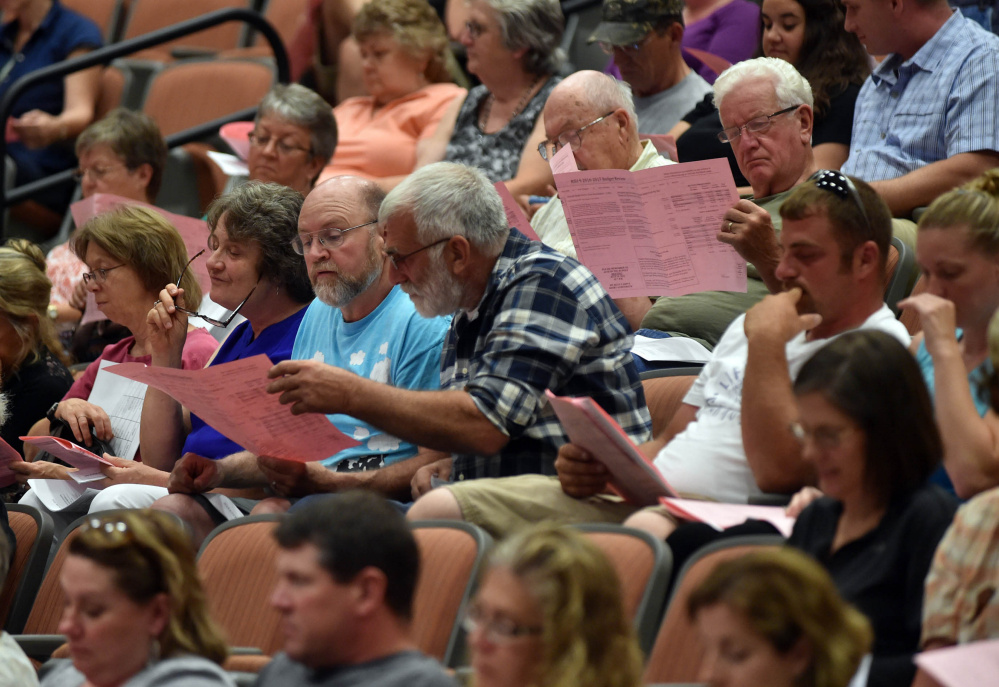 Regional School Unit 9 districtwide meeting participants examine budget documents Thursday at Mt. Blue High School in Farmington on Thursday.