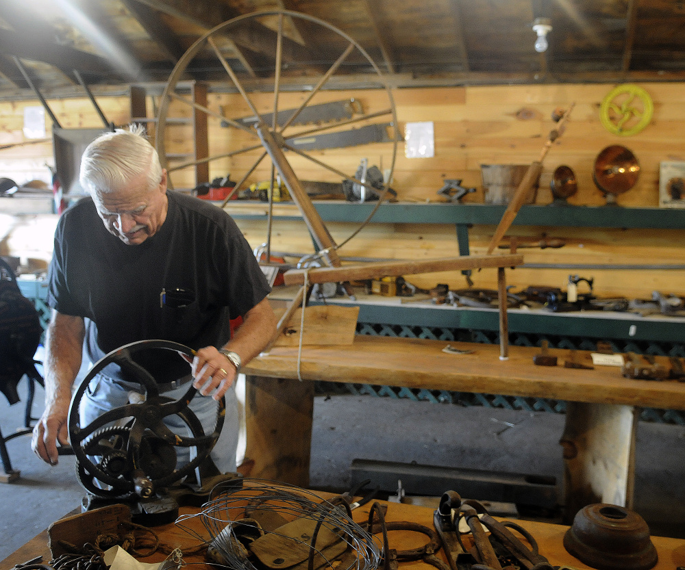 Dick Harriman sets up items for display Tuesday in the museum at the Pittston Fair.