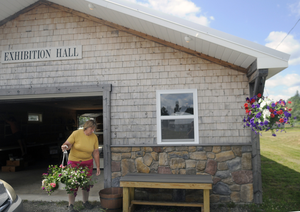 Jean Ambrose hangs flower baskets Tuesday on the exterior of the Exhibition Hall at the Pittston Fair, which runs Thursday through Sunday.