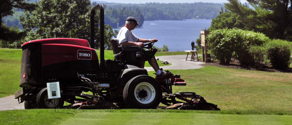 Mike Nadeau drives a rough mower at the Augusta Country Club on Wednesday in Manchester.