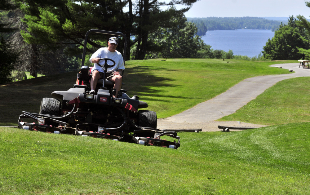 Mike Nadeau drives a rough mower at the Augusta Country Club on Wednesday in Manchester. A lot of prep work goes into getting the course ready for a big tournament like the Charlie's Maine Open that gets under way Monday.