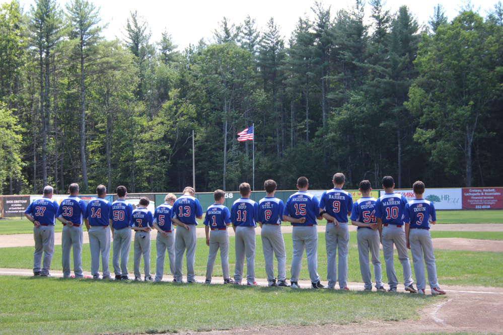 Members of the Augusta 13 Babe Ruth team stand at attention prior to its New England regional game against Taunton, Massachusetts, on Tuesday.