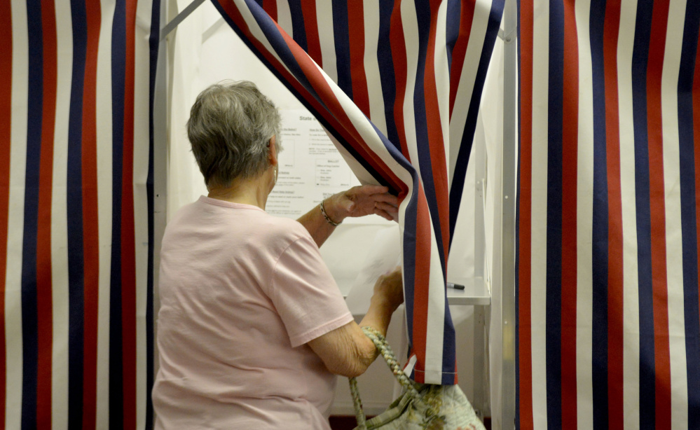 Mary Harris, of New Sharon, enters a voting booth Thursday to cast a ballot on the Regional School Unit 9 school budget at the New Sharon Town Office.