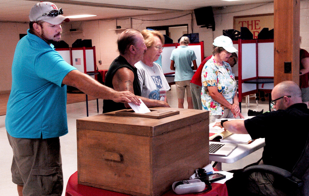 Mark Simpson casts his vote Thursday on the Regional School Unit 9 budget as other voters receive ballots at the Farmington Community Center in Farmington. The 10 towns in the district voted for the second time this summer on the budget, which passed.