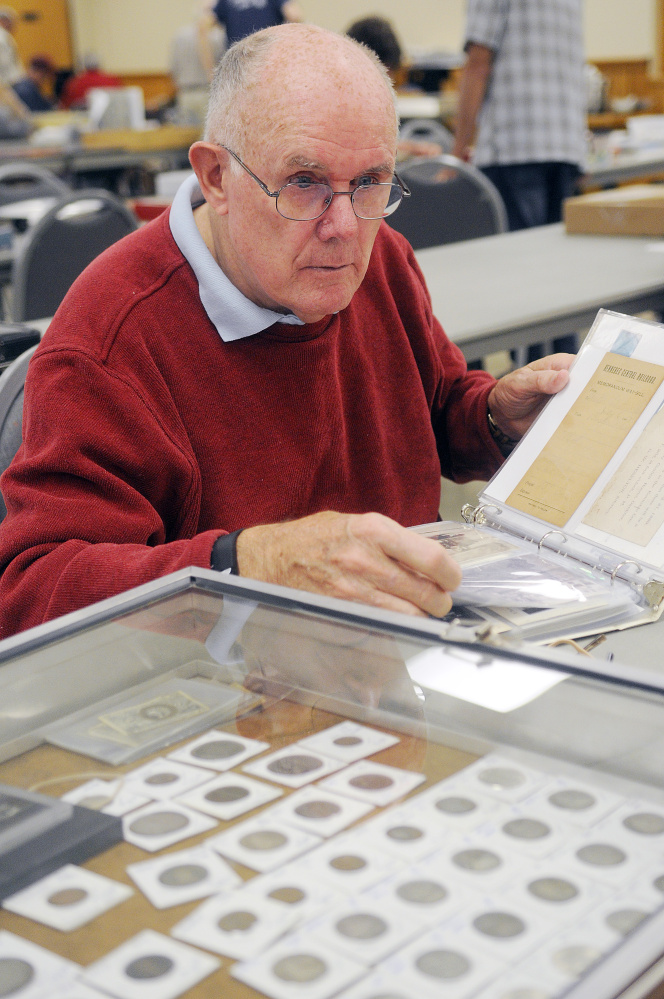 Frank Trask, of Farmingdale, assesses a collection Sunday at the Capital City Coin Show, held at the Elks Lodge in Augusta.