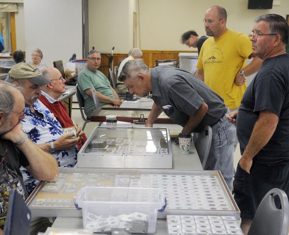People look at antique currency on display Sunday at the Capital City Coin Show, held at the Elks Lodge in Augusta.