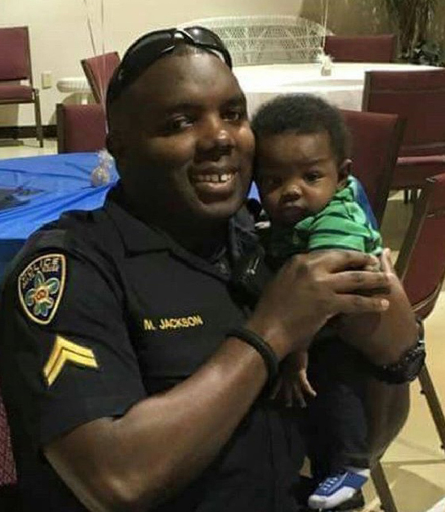 Police Officer Montrell Jackson holds his son, Mason, at a Father's Day event for police officers in Baton Rouge, La.