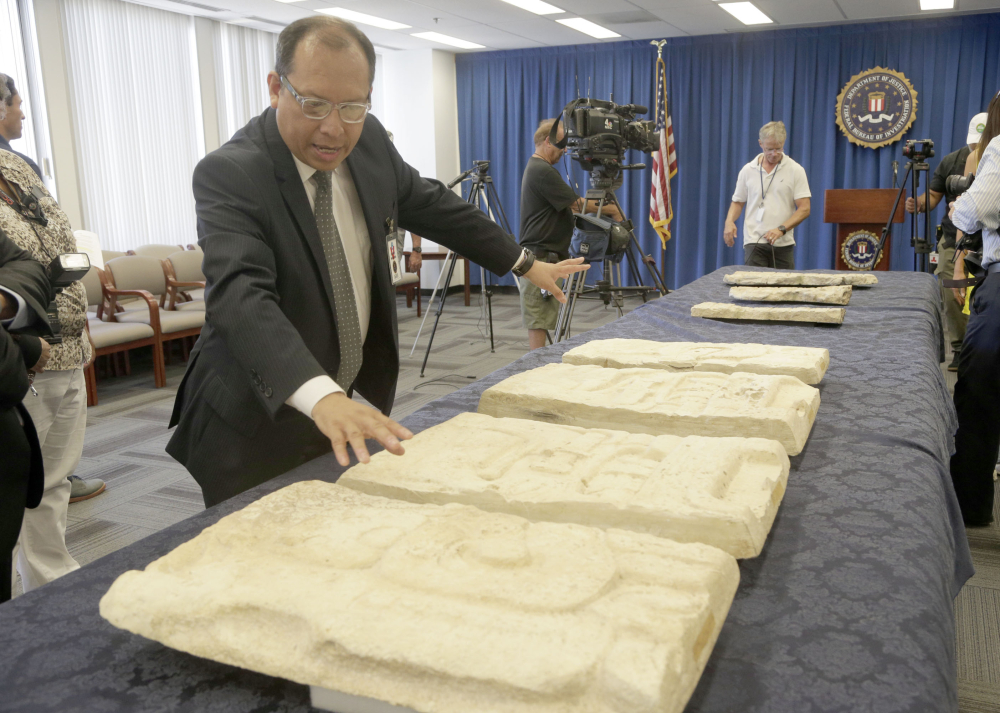 Los Angeles-based Consul General of Guatemala Roberto Archila reviews pre-Columbian Mayan artifacts during a repatriation ceremony at FBI offices Friday in Los Angeles.