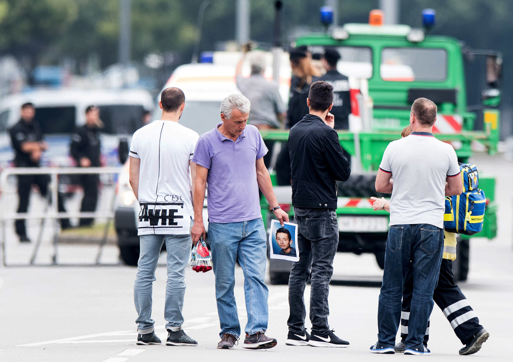 The father of a victim, center, holds a picture of his son near the Olympia shopping center where a gunman on Friday killed nine people and himself, on Saturday in Munich, Germany.