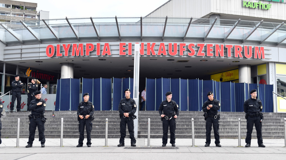 Police officers stand in front of the Olympia mall on Saturday in Munich, Germany, one day after an 18-year-old gunman opened fire at the crowded Munich shopping center and fast-food restaurant and killed nine people before killing himself.