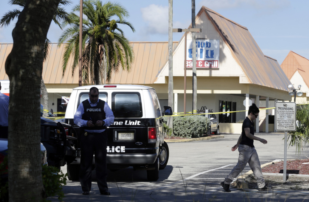 Officials investigate the scene of a deadly shooting outside the Club Blu nightclub, Monday, July 25, 2016, in Fort Myers, Fla. Gunfire erupted at the nightclub hosting a swimsuit-themed party for teens.