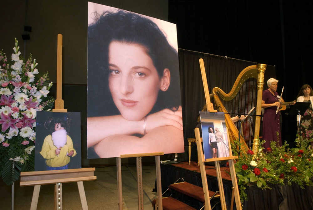 Photos of Chandra Levy are on display at her memorial service in 2002. Police initially had suspected then-California Rep. Gary Condit in her killing.