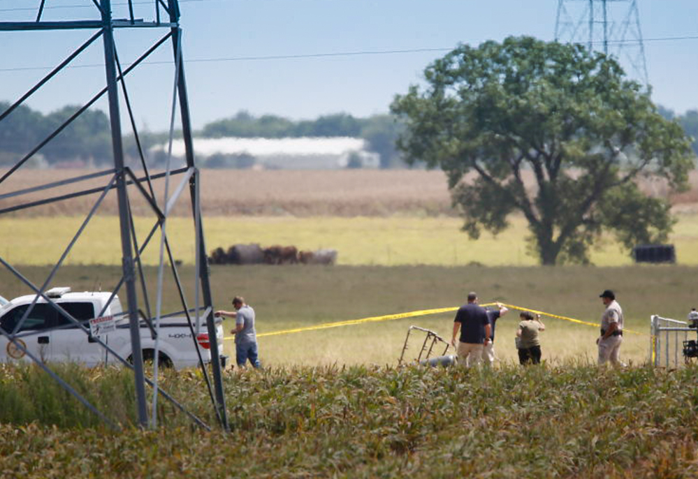 Investigators surround the scene in a field near Lockhart, Texas, where a hot air balloon carrying 16 people collided with power lines Saturday.