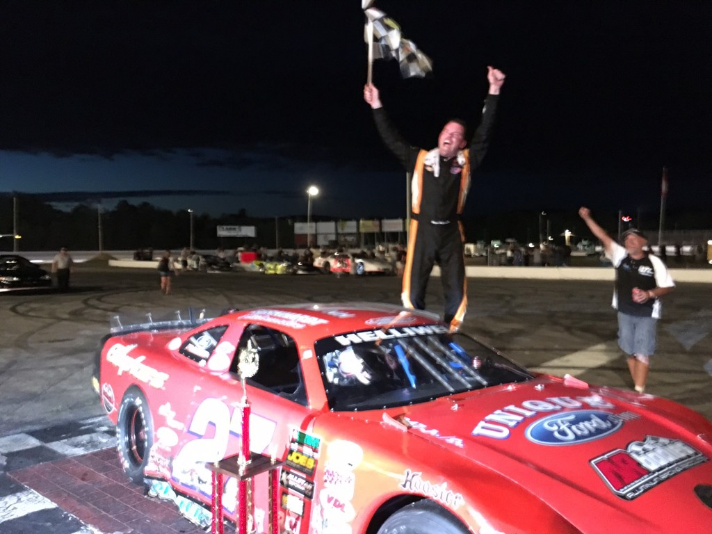 Wayne Helliwell Jr. of Dover, New Hampshire, celebrates winning the PASS HP Hood 150 on Sunday night at Oxford Plains Speedway in Oxford.