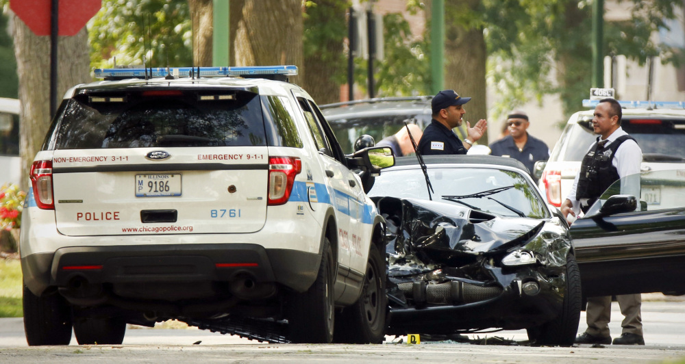 Chicago police investigate a police-involved fatal shooting in Chicago's South Shore neighborhood on July 29. Police say they shot and killed an 18-year-old man who was in a stolen Jaguar that sideswiped a squad car.  Jose M. Osorio/Chicago Tribune via AP File