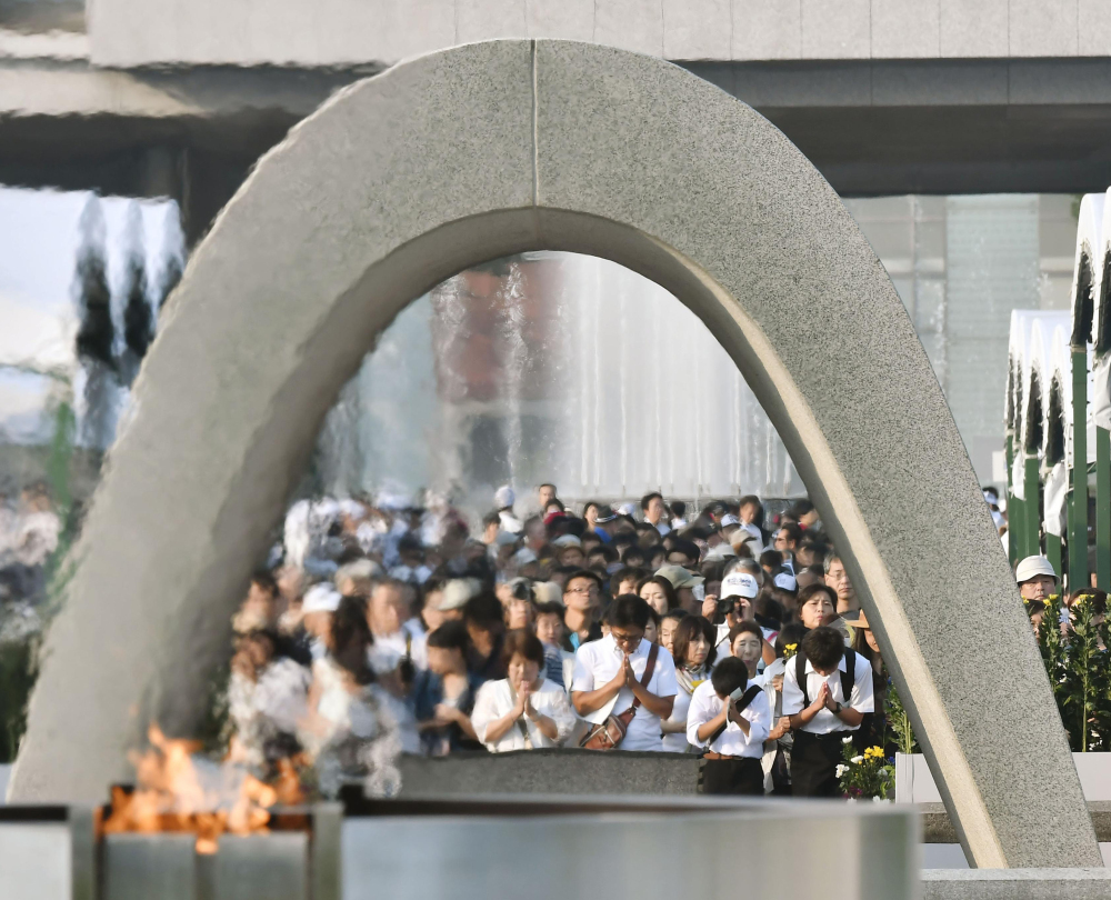 People pray for the atomic bomb victims in front of the cenotaph at the Hiroshima Peace Memorial Park in Hiroshima on the 71st anniversary of the bombing Saturday.