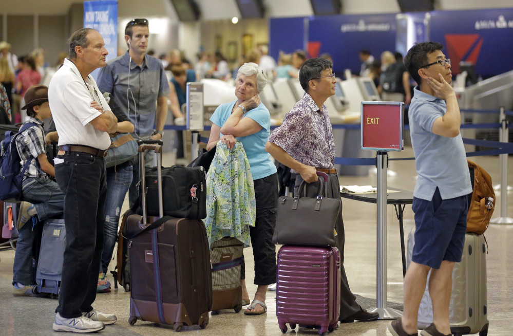 Passengers stand in line Tuesday in Salt Lake City as Delta Air Lines slogged through a second day of its recovery from a global computer outage. Portland's jetport also reported canceled and delayed Delta flights Tuesday.