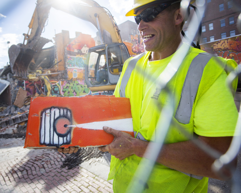 Workers demolish a graffiti wall on Free Street in Portland on Monday. Harry Fillmore of Benjamin Construction holds a piece of the mural.