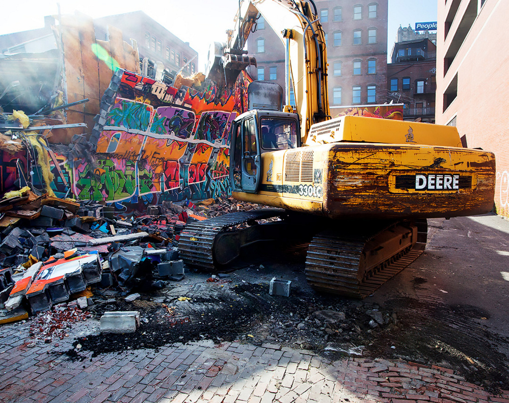 Workers demolish the famed graffiti mural at Asylum in Portland on Monday.