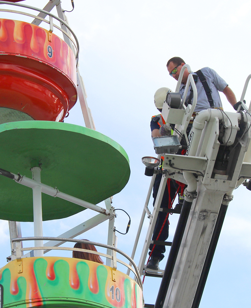 Members of the Greeneville Fire Department help people off the Ferris wheel from which three children fell on Monday during a county fair in Greeneville, Tenn.