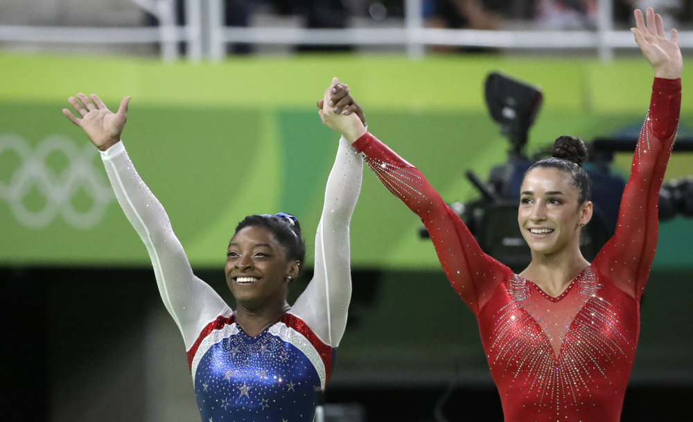 Simone Biles, left, and her teammate Aly Raisman celebrate after winning the gold and silver medals, respectively, in the artistic gymnastics all-around final Thursday.