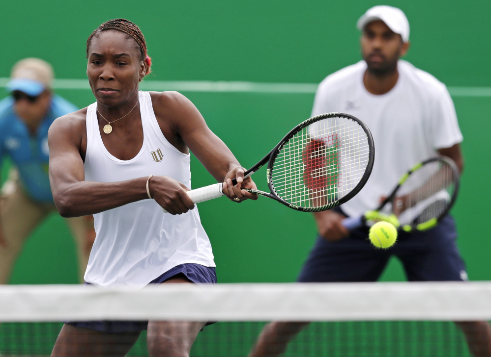 Venus Williams, seen playing with Rajeev Ram in Thursday's mixed doubles match against the Netherlands, reached the semifinals Friday in a win over Italy.