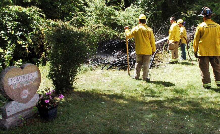Waterville firefighters extinguish fire in some brush July 21 beside gravesites at St. Francis Catholic Cemetery in Waterville. Police have charged a city man in connection with setting a pair of fires at the St. Francis and Pine Grove cemeteries that day.