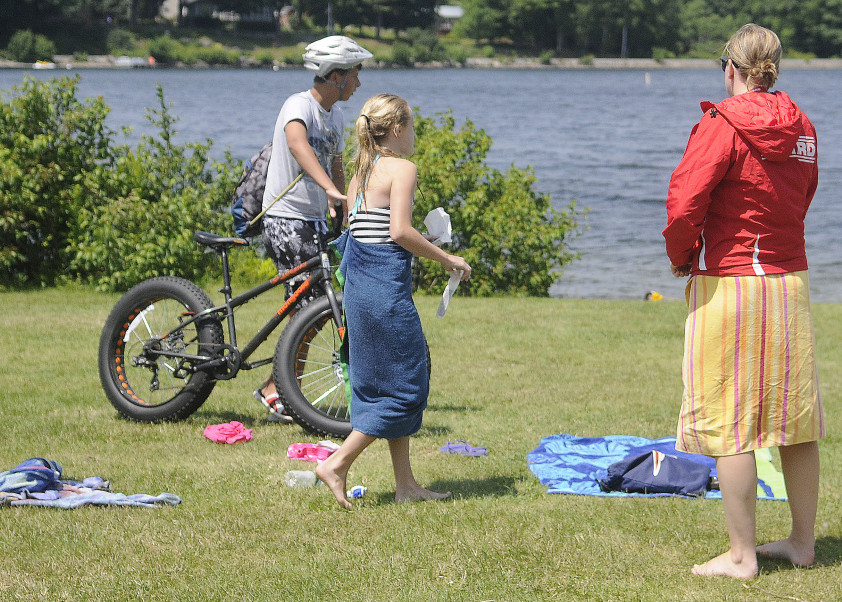 Lifeguard Elizabeth Preble, right, speaks to visitors July 20 at the town beach on Maranacook Lake in Winthrop. The Town Council voted Monday night to spend money on a bike patrol at the beach and in the downtown area for the rest of summer to address concerns about vandalism and other disturbances.