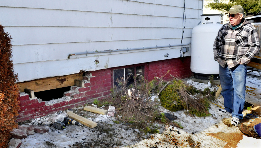 Waterville homeowner Roland Hallee looks over the damage to a basement wall on March 6 that occurred when a vehicle driven by Sueann M. Call, 47, of Waterville, crashed into the building.